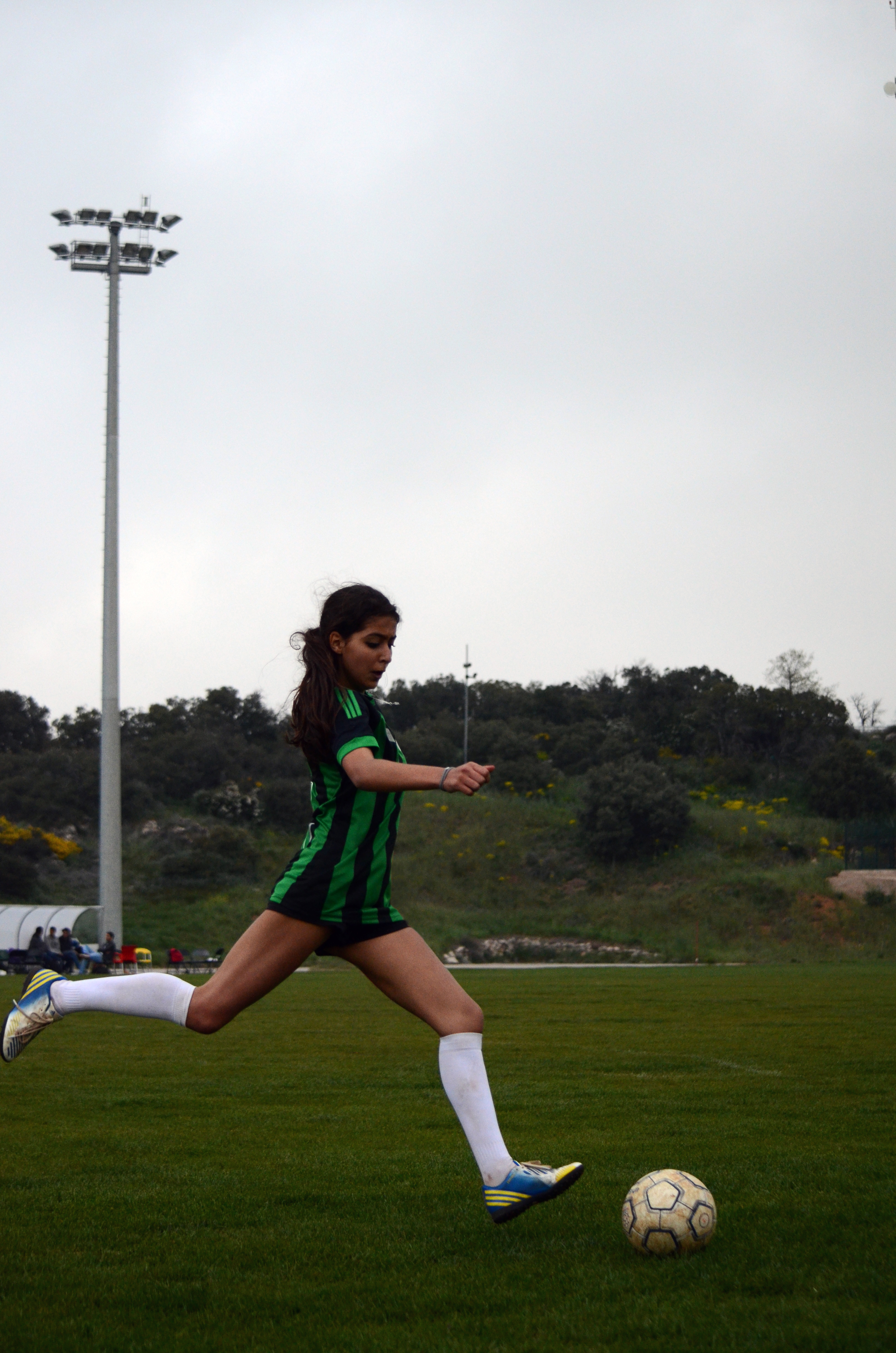 A young woman in a black and green jersey making a dynamic play at a soccer game.